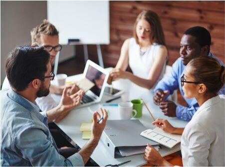 5W2H. Imagem decorativa de jovens conversando em ambiente de trabalho.